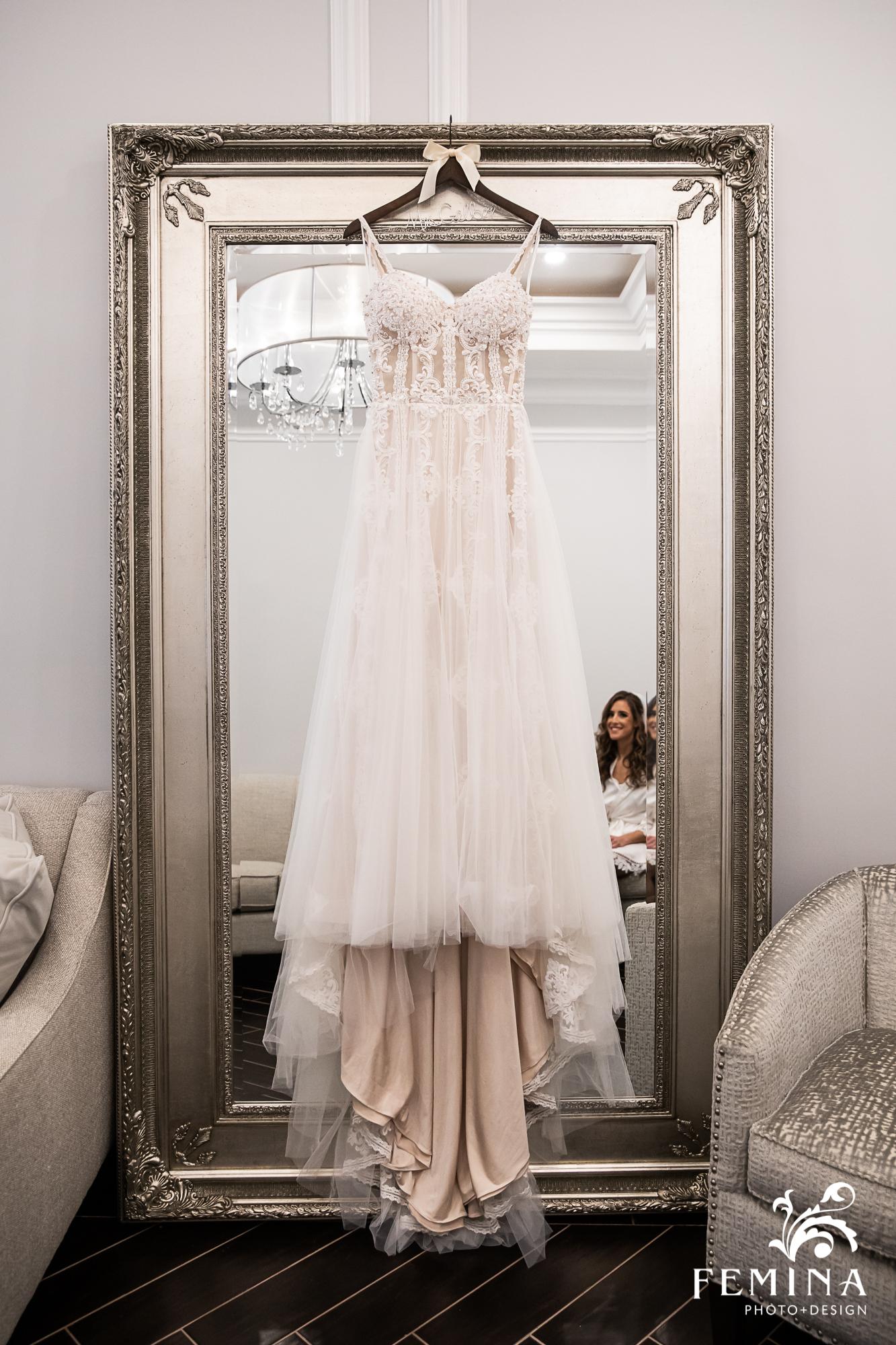 Bride's wedding dress hanging on a mirror